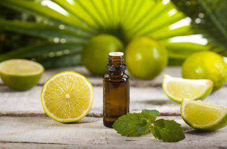 Foto de Bottle of essential oil from limes on wooden table and green leaves background - alternative medicine - Imagen libre de derechos