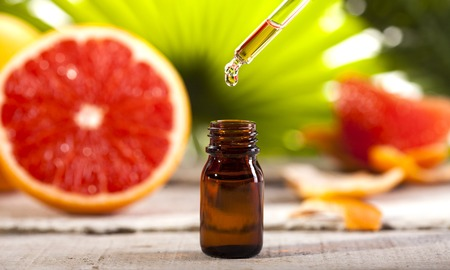 Photo pour Bottle of essential oil from grapefruits on wooden table and green leaves background - alternative medicine - image libre de droit