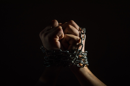 Foto de Hands are chained in chains isolated on black background - Imagen libre de derechos