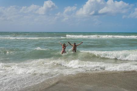 Foto de Young couple in love bathes and have fun in the sea - Imagen libre de derechos