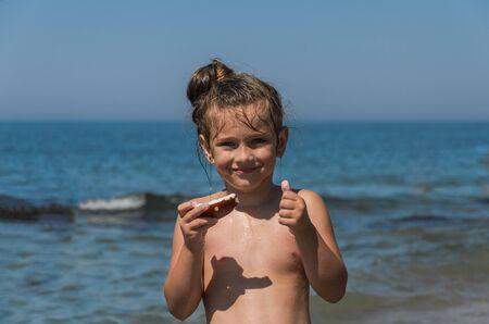 Photo pour Little charming girl child eating coconut on the sea beach - image libre de droit