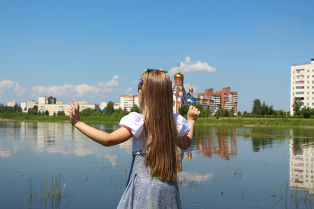 Photo for Girl seven years is streching out her hands and standing on the lakeshore - Royalty Free Image