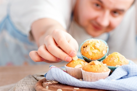 Photo for Chef is decorating delicious organic muffins  Almond and cherry cup cakes in natural setting  - Royalty Free Image