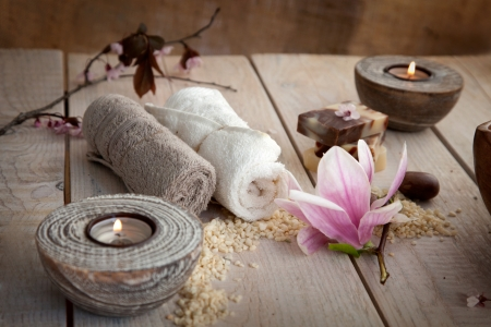Spa and wellness setting with natural soap, candles and towel. Beige dayspa nature set