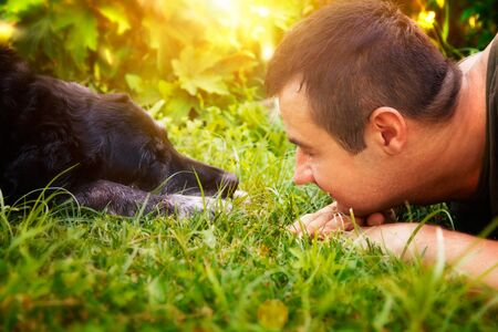 Friends concept Man and labrador retirever dog are lying in summer grass
