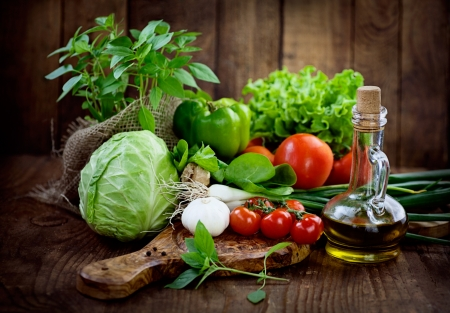 Foto de Fresh ingredients for cooking in rustic setting: tomatoes, basil, olive oil, garlic and onion,cabbage,letttuce - Imagen libre de derechos
