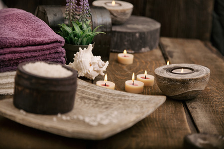 Photo for Spa and wellness setting with natural bath salt, candles, towels and flower. Wooden dayspa nature set - Royalty Free Image