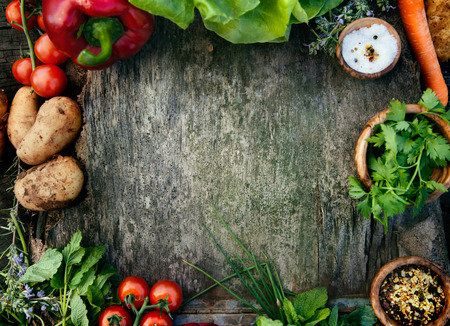Healthy food ingredients background. Vegetables, herbs and spices. Organic vegetables on wood