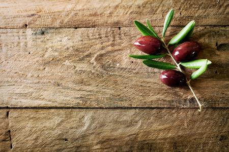Foto de Olives on olive branch. Wooden table with olives - Imagen libre de derechos