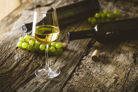 Photo pour Wine. Glass of white wine in wine cellar. Old white wine on wood. - image libre de droit