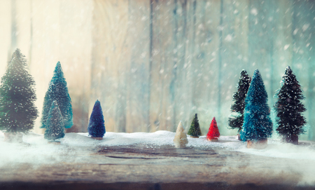 Foto de Christmas trees on wood. Christmas background with snow. Small xmass trees - Imagen libre de derechos
