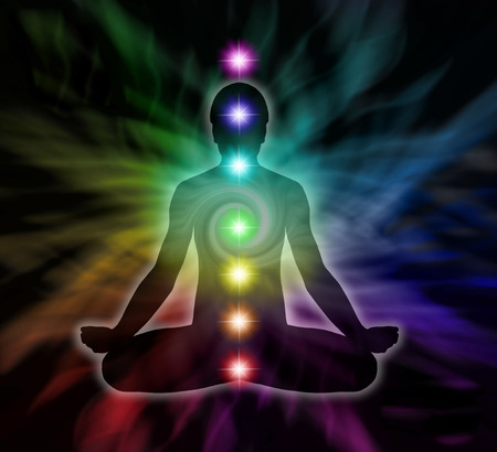 Foto de Silouette of a man in lotus meditation position with Seven Chakras on flowing rainbow energy background - Imagen libre de derechos