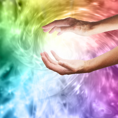 Photo pour Outstretched healing hands on vivid rainbow vortex swirling energy background - image libre de droit