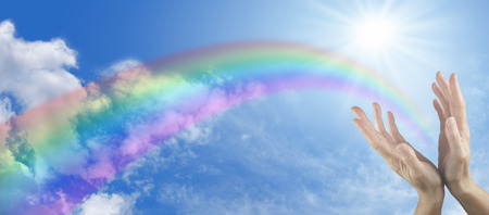 Foto de Panoramic blue sky with sunburst, rainbow and two hands reaching up - Imagen libre de derechos