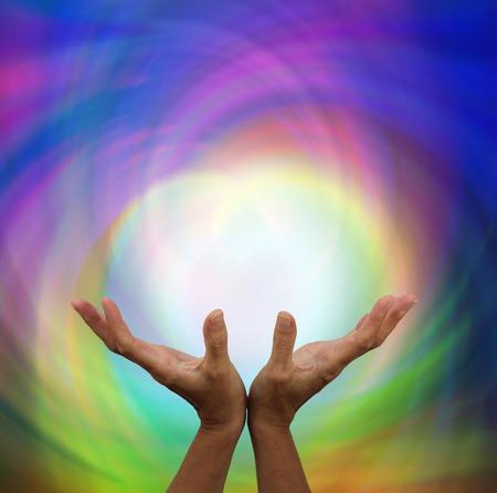 Foto de Outstretched healing on rainbow energy colour background - Imagen libre de derechos