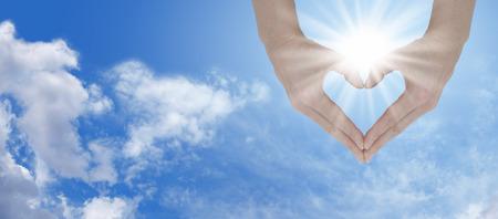 Foto de   Hands holding the sunshine and create heart shape  - Imagen libre de derechos