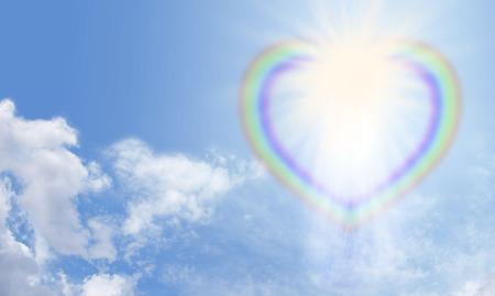 Foto de Heart rainbow bursting with light on a blue sky - Imagen libre de derechos