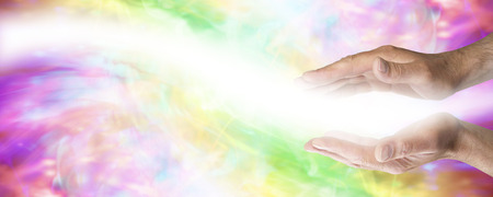 Foto de Male parallel healing hands with light wave passing on colored banner background - Imagen libre de derechos