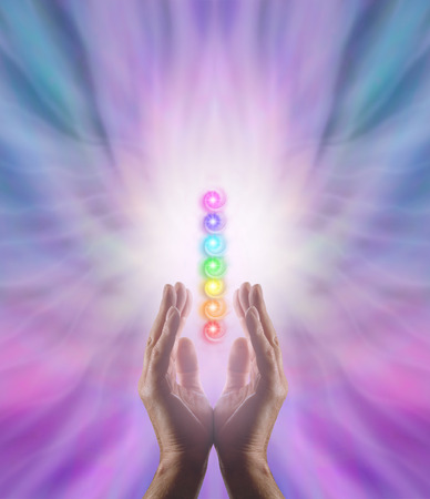 Foto de Sending Chakra Healing Energy - Male parallel hands facing upwards with white energy and the Seven Chakras floating between on a pink and blue ethereal energy formation background - Imagen libre de derechos