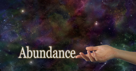 Photo for Universal Abundance - Female hand facing up with the word Abundance touching the index finger on a deep space night sky background providing plenty of copy space above - Royalty Free Image