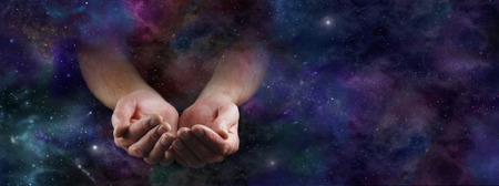 Photo for Our Abundant Universe - Male hands emerging from a wide dark deep space background gesturing with cupped hands - Royalty Free Image