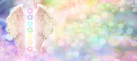 Photo for Reiki Angel Wings and Seven Chakras website header -  Angel wings and seven chakras on pastel rainbow colored bokeh  background with copy space on right hand side - Royalty Free Image