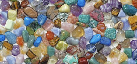 Photo pour Multicolored tumbled crystal stones background - a large quantity of different colored healing tumbled gem stones making up a backdrop for use as a background - image libre de droit