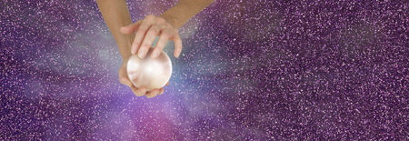 Photo for Fortune Teller holding crystal ball on sparkling banner - Female fortune teller holding a large  crystal ball in cupped hands against a sparkling magenta  background with copy space - Royalty Free Image