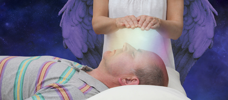 Foto de Angelic help during a healing session - female hands hoovering above a male patient's face channeling energy together with a higher power in the background depicting Angelic help - Imagen libre de derechos