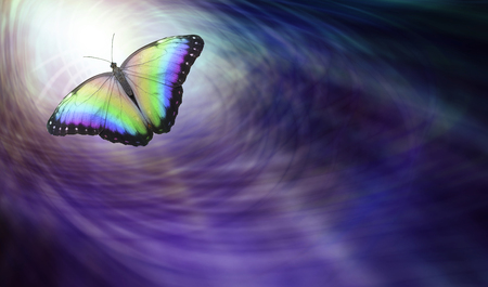 Foto de Symbolic Spiritual Release -  Beautiful multicoloured butterfly moving into the light depicting a departing soul - Imagen libre de derechos