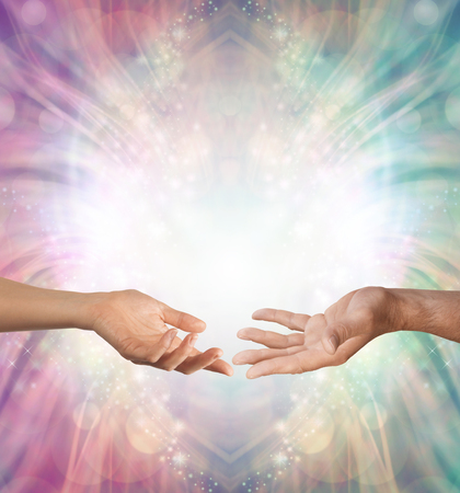 Photo pour Male and Female energy merging - a female hand and a male hand with open palms facing each other against a beautiful intricate masculine and feminine colored energy background with copy space above - image libre de droit