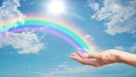 Photo for female hand with a bright rainbow arcing across a blue sky with fluffy clouds and a bright sun burst - Royalty Free Image