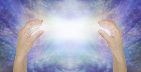 Foto de Sending pure unconditional love healing energy - female hands opposite each other with a bright white light beam between against a shimmering blue sparkle background - Imagen libre de derechos