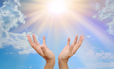 Foto de Healing website header - healer's hands outstretched reaching up towards a bright sunburst beaming down with blue sky and fluffy clouds - Imagen libre de derechos