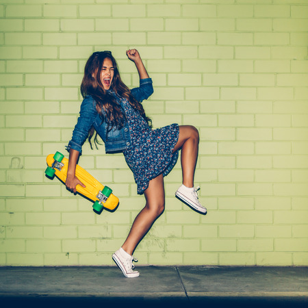 Photo for young happy beautiful long-haired brunette girl in blue dress having fun with yellow plastic penny board skateboard in front of the green brick wall - Royalty Free Image