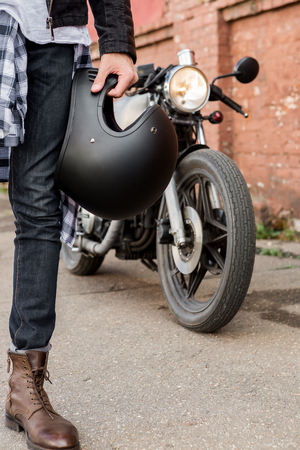 Photo pour Close-up of a handsome rider biker man hand with black helmet in front of classic style cafe racer motorcycle. Bike custom made in vintage garage. Brutal fun urban lifestyle. Outdoor portrait. - image libre de droit