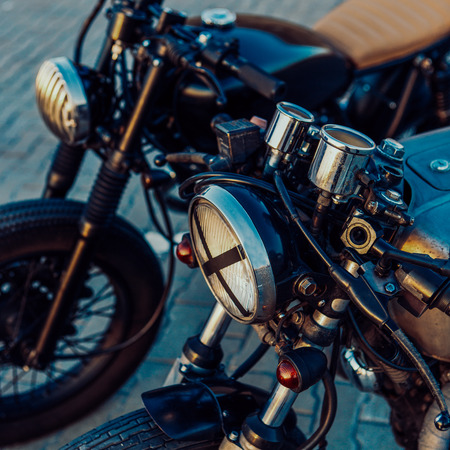 Photo for Two vintage custom motorbike motorcycle cafe racer one with grill headlight another with tape cross over optic on empty rooftop parking lot during sunset. Hipster lifestyle. Lamp lights turned on. - Royalty Free Image
