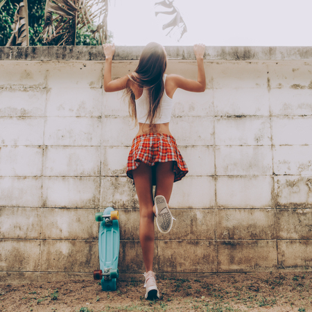 Photo pour Sporty young woman with sexy ass in a red tartan mini skirt with blue penny skateboard trying to climb over the fence of a tropical garden. Outdoor lifestyle picture on a sunny summer day. - image libre de droit