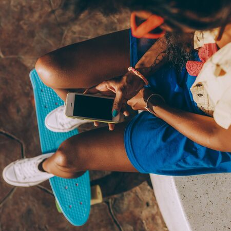 Foto de Outdoor lifestyle close-up of black sporty lady in bright outfit and sunglasses. Young hipster girl sitting at skate park and texting on her smartphone. She is happy. Sunny summer day. Swag, fashion. - Imagen libre de derechos
