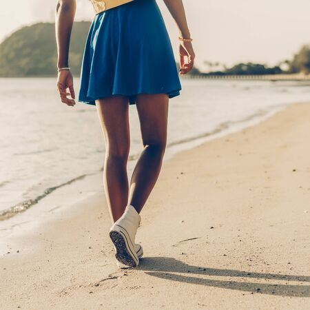 Foto de Beautiful sporty black  in blue skirt walk at tropical ocean shore with golden sand. Outdoor lifestyle close up of  long legs in white  sneakers. Sunny hot summer day. Swag, fashion. - Imagen libre de derechos