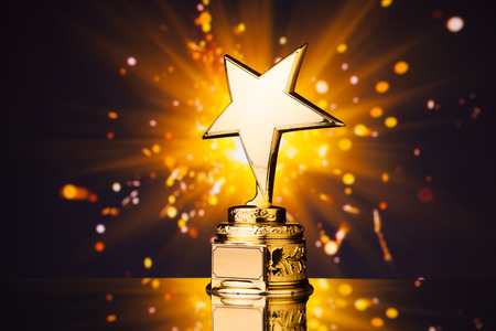 Photo for gold star trophy against shiny sparks background - Royalty Free Image