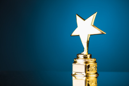 Foto de gold star trophy against blue background - Imagen libre de derechos