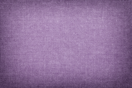 Foto de Dark violet background from a textile material with wicker pattern, closeup. Structure of the light lilac fabric with texture. Cloth lavender backdrop with vignette. - Imagen libre de derechos