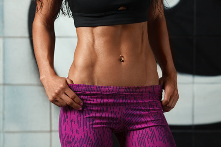 Photo for Fitness sexy woman showing abs and flat belly. Beautiful muscular girl, shaped abdominal, slim waist - Royalty Free Image