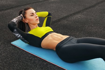 Photo pour Fitness woman doing sit ups in the stadium working out. Sporty girl exercising abdominals, outdoor - image libre de droit