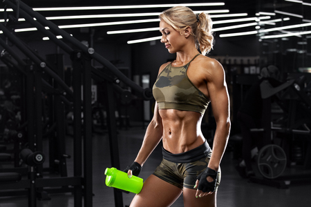 Foto de Athletic girl with shaker in gym. Fitness woman with flat belly, shaped abdominal, abs - Imagen libre de derechos