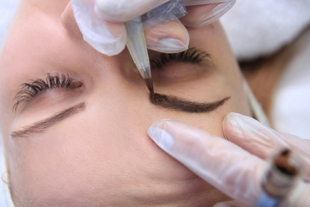 Photo pour Cosmetologist applying permanent make up on eyebrows eyebrow tattoo - image libre de droit