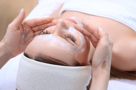 Photo pour Beautician makes cleansing and exfoliating facial for beautiful girl. Beauty salon. - image libre de droit
