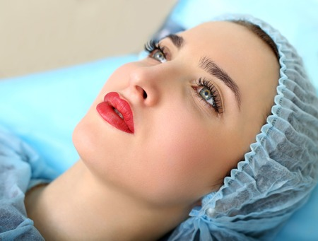 Foto de Healthy Spa: Young Beautiful Woman Having Permanent Make-up Tattoo on her Lips. Close-up - Imagen libre de derechos