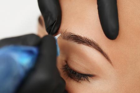 Foto de Cosmetologist applying permanent make up on eyebrows- eyebrow tattoo - Imagen libre de derechos